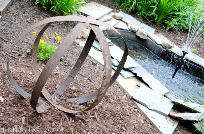 DIY: Outdoor Sculpture using metal straps from an old barrel.  Big impact with little work + no cost!