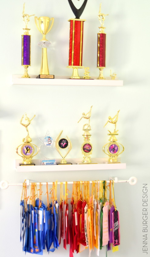 Hang ribbons using an inexpensive curtain rod + floating shelves for awards!